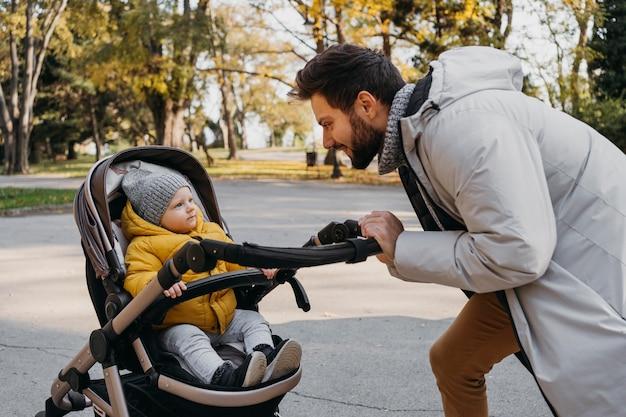 Hombre feliz con su hijo afuera en cochecito