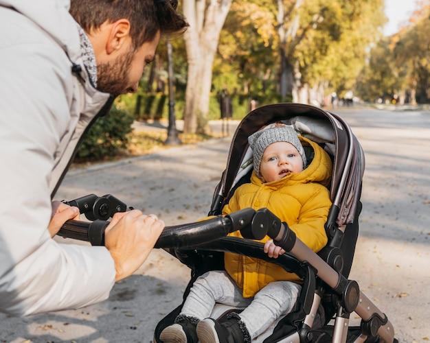 Hombre feliz con su hijo afuera en la naturaleza