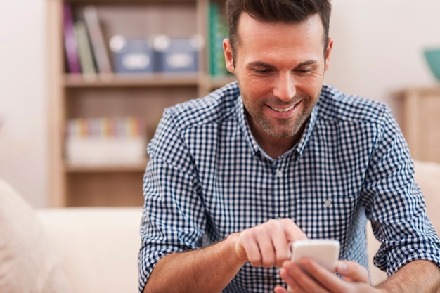 Hombre feliz con teléfono móvil en casa en la sala de estar