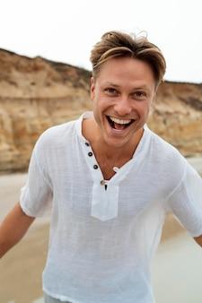 Hombre feliz de tiro medio en la playa