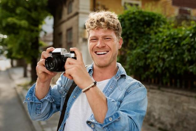 Hombre feliz de tiro medio sosteniendo la cámara