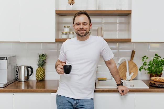 Hombre feliz tomando café en la cocina