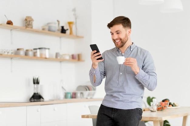 Hombre feliz tomando café mientras revisa el móvil