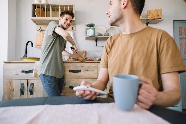 Hombre feliz trabajando en la cocina mirando a su amigo usando un teléfono móvil