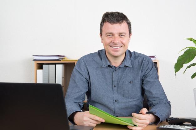 Hombre feliz trabajando en una computadora portátil en brillante