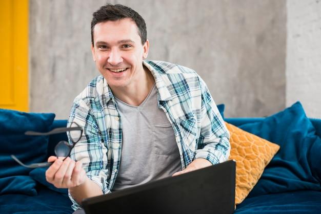 Hombre feliz trabajando en la computadora portátil en la sala de estar