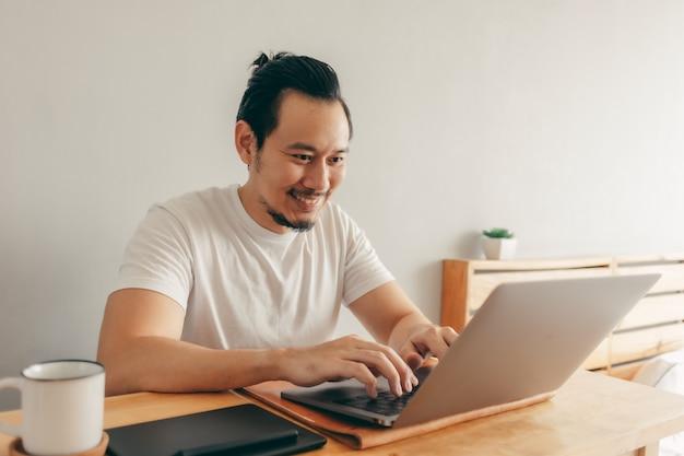 Hombre feliz está trabajando en su apartamento en concepto de trabajo desde casa.