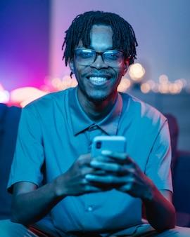 Hombre feliz usando su teléfono inteligente mientras está en casa