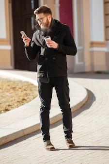 Hombre feliz usando teléfono celular y tomando café en la ciudad