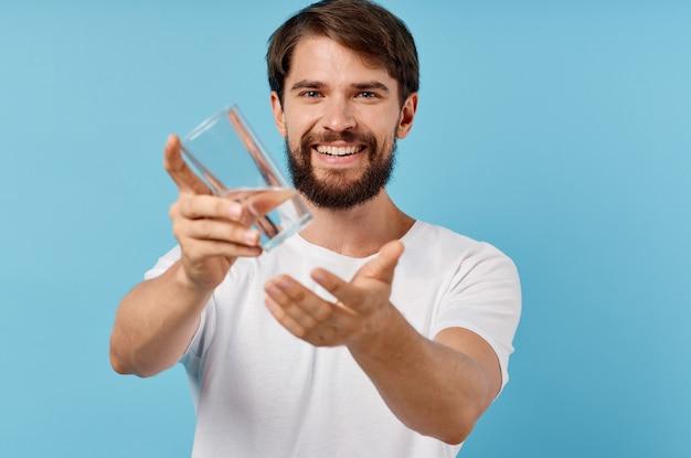 Hombre feliz con vaso de agua sobre fondo azul bebida estilo de vida.