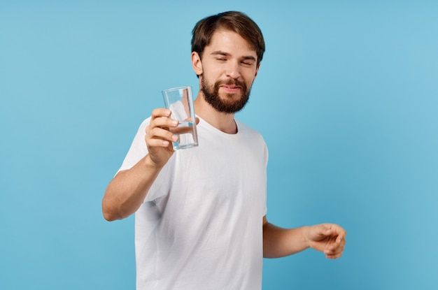Hombre feliz con vaso de agua sobre fondo azul bebida estilo de vida