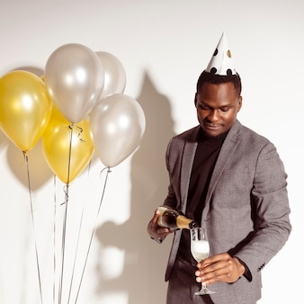 Hombre feliz vertiendo champán en vidrio
