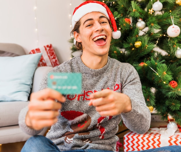 Hombre festivo apuntando a tarjeta de crédito