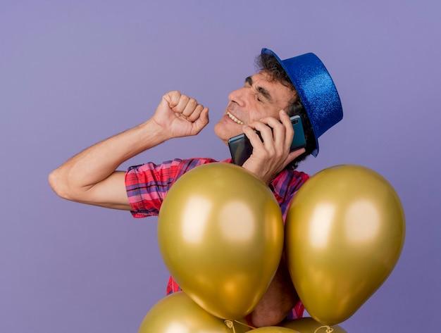 Hombre de fiesta de mediana edad sonriente con sombrero de fiesta de pie detrás de globos hablando por teléfono manteniendo el puño en el aire con los ojos cerrados aislados en la pared púrpura