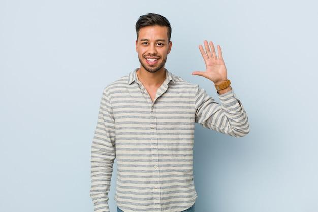 Hombre filipino hermoso joven que sonríe alegre mostrando el número cinco con los dedos.