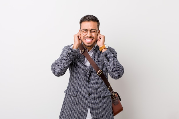 Hombre filipino joven del negocio contra una pared blanca que cubre los oídos con las manos.