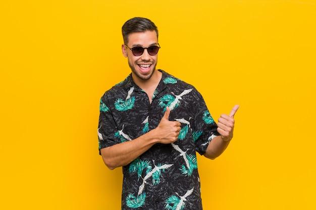 Hombre filipino joven con ropa de verano levantando ambos pulgares, sonriendo y confiado.