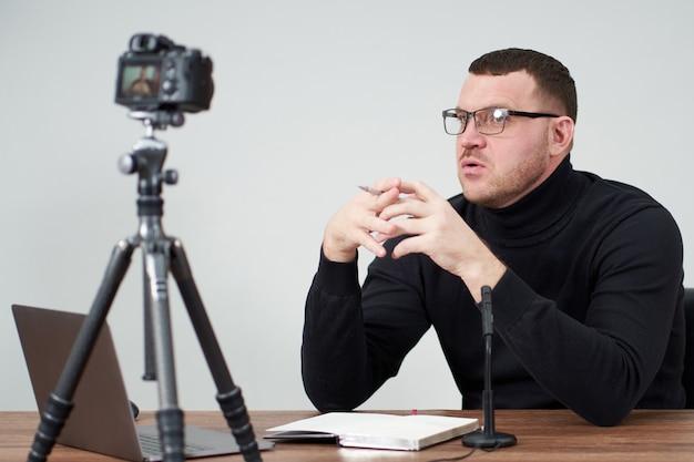 Hombre filmando video blog en cámara con trípode para seguidores en línea. en redes sociales, influencer, nuevas tecnologías, comunicación e internet.
