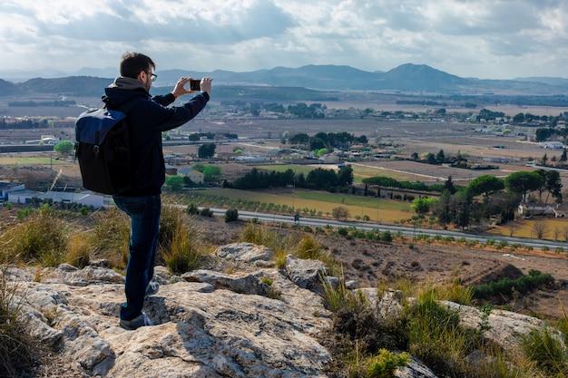 El hombre está filmando un video de una hermosa puesta de sol en un teléfono celular