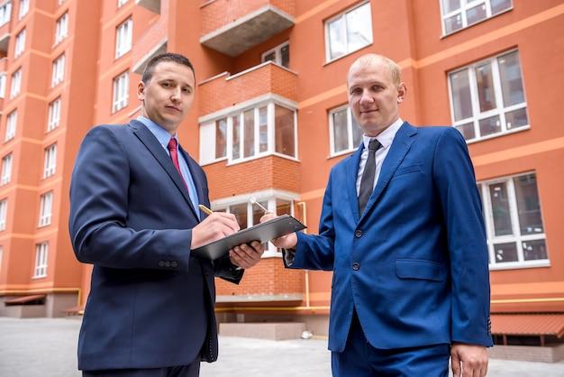 El hombre firma el contrato de compra de apartamento frente al nuevo edificio