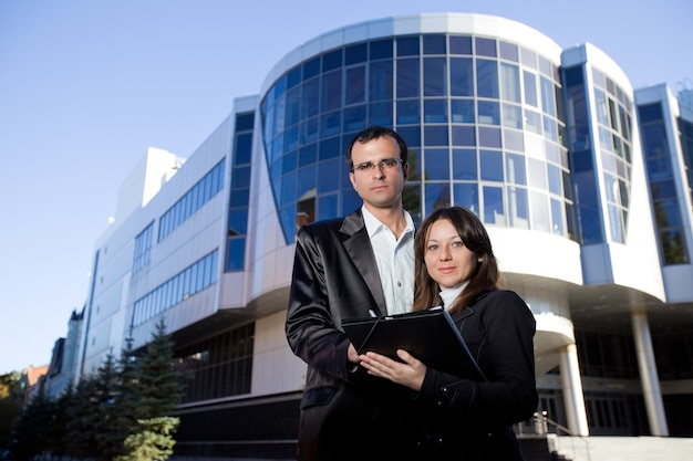 El hombre firma documentos en manos de la mujer mientras está de pie en la calle frente al edificio de oficinas