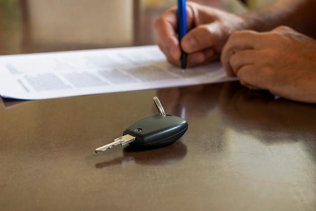Hombre firmando un coche de alquiler o un documento de seguro en papel. firma escrita en contrato o convenio.