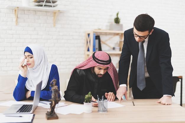 El hombre está firmando papeles de divorcio en la oficina del abogado