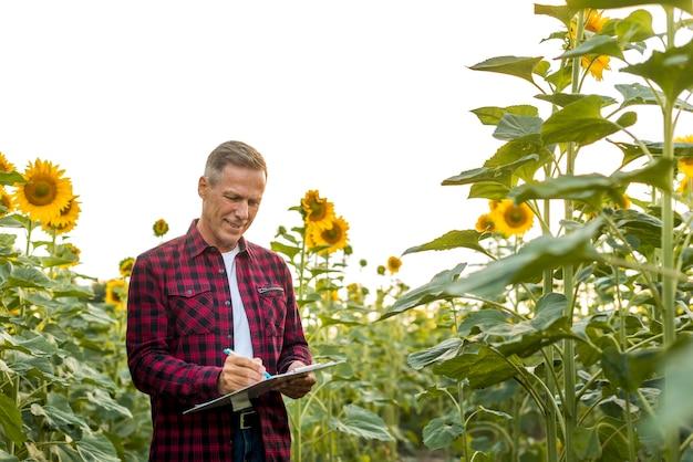 Hombre firmando en un portapapeles en un campo