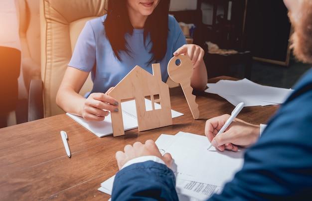 Hombre firmar una póliza de seguro de hogar sobre préstamos para la vivienda. agente inmobiliario con el cliente antes de la firma del contrato.