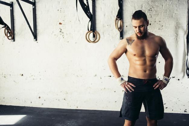 Hombre físicamente en forma posando en un club de salud