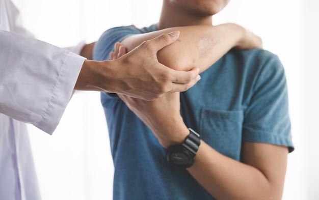 Un hombre de fisioterapia de rehabilitación moderna en el trabajo con un cliente hombre