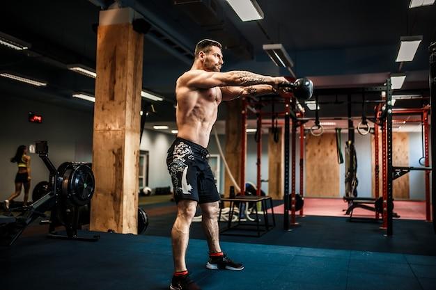 Hombre fitness balanceando pesas rusas en el gimnasio