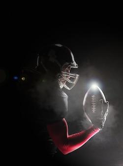 Hombre de fitness caucásico como jugador de fútbol americano sosteniendo una pelota sobre fondo negro