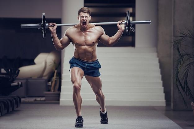 Hombre fitness culturista bombeo de los músculos de las piernas