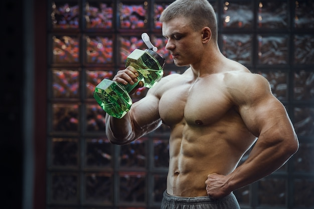 Hombre de fitness en el gimnasio de agua potable después del entrenamiento mirando teléfono celular