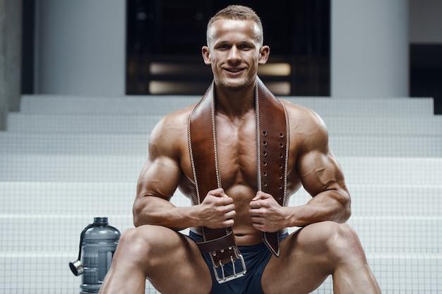 Hombre de fitness en el gimnasio de agua potable después del entrenamiento