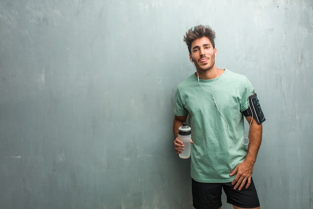Hombre fitness joven contra una pared de grunge expresión de confianza y emoción, divertido y amigable