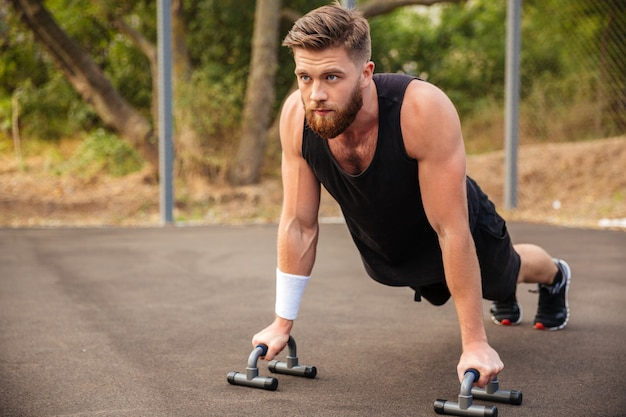 Hombre fitness musculoso haciendo flexiones y usando equipos deportivos al aire libre