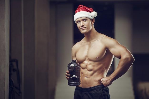 Hombre fitness en traje de sombrero de santa claus en gimnasio con teléfono celular