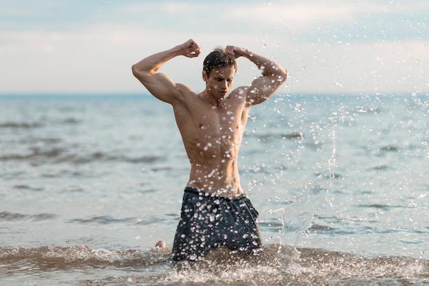 Hombre flexionando sus bíceps en agua.