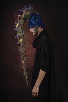 Un hombre con flores azules en un cuarto oscuro