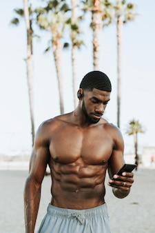 Hombre en forma escuchando música mientras está en la playa