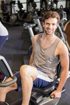 Hombre en forma haciendo bicicleta de ejercicio en el gimnasio