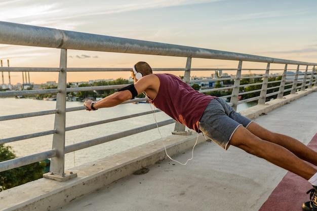 Hombre en forma haciendo ejercicio en el puente, llevando una vida sana.