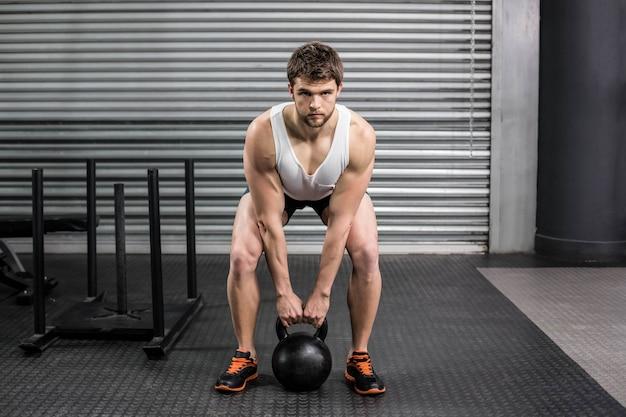 Hombre en forma levantando pesas en el gimnasio crossfit