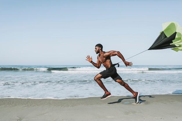 Hombre en forma con un paracaídas corriendo en la playa