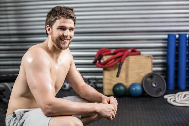 Hombre en forma tomando un descanso de hacer ejercicio en el gimnasio de crossfit