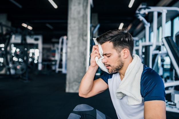 Hombre en forma tomando un descanso de hacer ejercicio en el gimnasio.