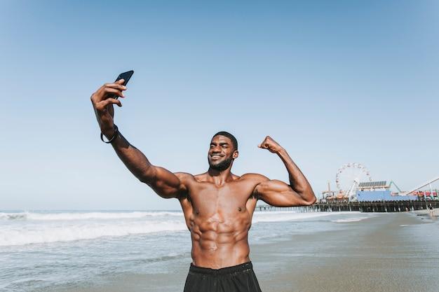Hombre en forma tomando un selfie por el muelle de santa mónica