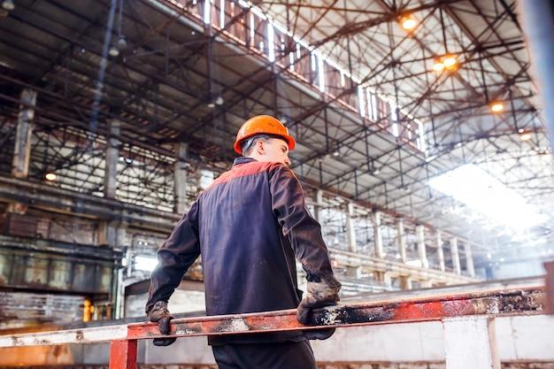 Un hombre en una forma de trabajo en una planta metalúrgica. cansado del trabajo trabajador.